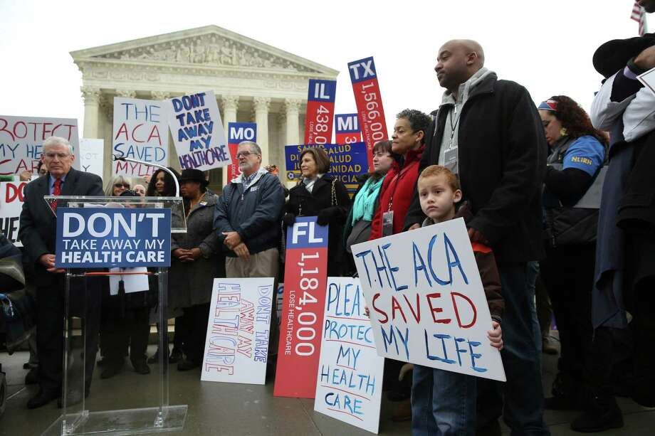 James Cook, of Cleveland, and his son Jumaane, 5, stand with signs amongst other protesters outside the Supreme Court on Wednesday morning in Washington, March 4, 2015. The fight over the Affordable Care Act returns to the Supreme Court as the justices hear arguments in a conservative challenge that could determine the future of the insurance program that now covers millions of people. (Doug Mills/The New York Times) ORG XMIT: XNYT4 Photo: DOUG MILLS / NYTNS