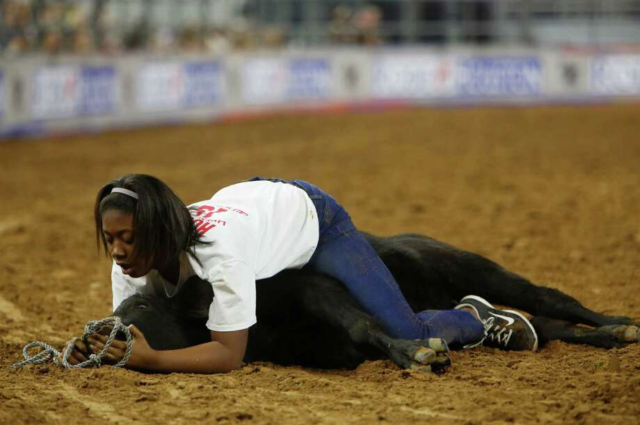 Alexandra Freeman wrestles with a calf during the calf scramble at the Houston Livestock Show and Rodeo Wednesday, March 4, 2015, in Houston. Photo: Jon Shapley, Houston Chronicle / © 2015 Houston Chronicle