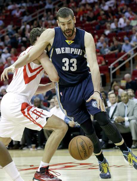 The Grizzlies' Marc Gasol (33) works to get around the Rockets' Donatas Motie-junas. Gasol had 21 points, including the game-winning shot in the last second. Photo: Pat Sullivan, STF / AP