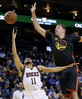 Milwaukee Bucks' Tyler Ennis, left, shoots against Golden State Warriors' David Lee (10) during the first half of an NBA basketball game Wednesday, March 4, 2015, in Oakland, Calif. (AP Photo/Ben Margot)