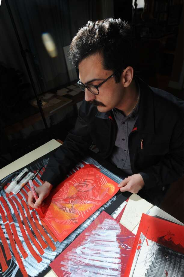 Carlo Busceme works on a drawing in his home studio in Beaumont. Busceme's work will be featured in the High Street Gallery inside Victoria House on Saturday. Photo taken Tuesday, February 24, 2015 Guiseppe Barranco/The Enterprise Photo: Guiseppe Barranco/The Enterprise