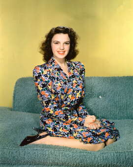 Judy Garland (1922-1969), wearing a floral print dress in a studio portrait, circa 1945.
