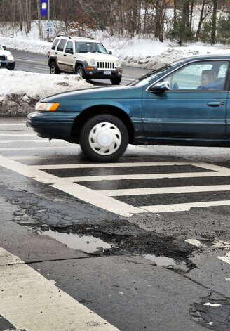 Potholes are a constant during any thaw. In this photograph from Feb. 8, 2011, shows cars trying to navigates around potholes at Fuller Road and Washington Avenue Extension Tuesday morning. (John Carl D'Annibale / Times Union)