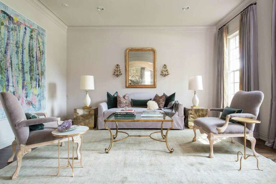 The formal sitting room features rich fabrics, fine art and bronze-toned details that can be found in nearly every room. Photo: Michael Hunter