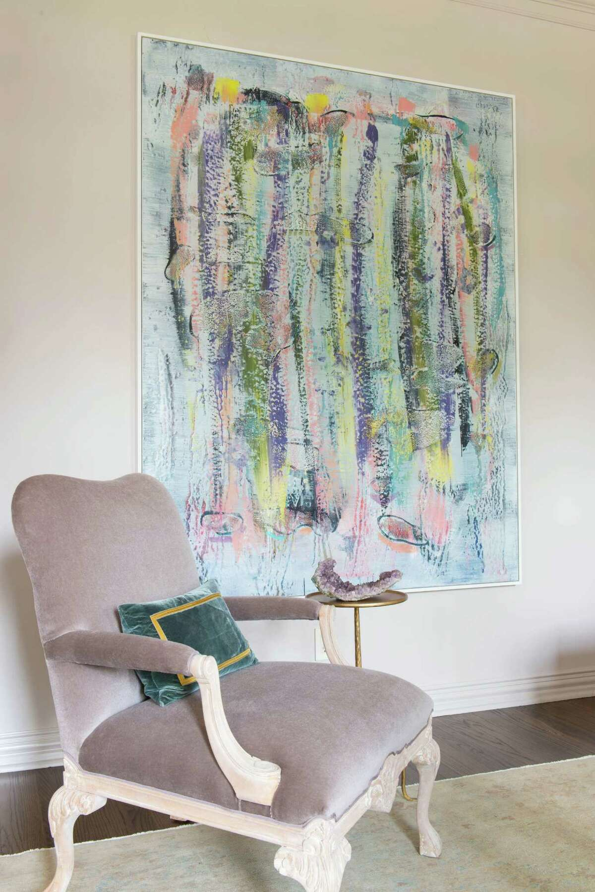 A painting by Jon Pestoni dominates one wall of the formal sitting room, adding a pop of color that coordinates with the room's pale neutrals.