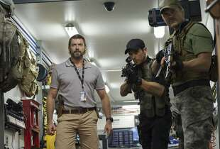 "This image released by Columbia Pictures shows Hugh Jackman, left, in a scene from ""Chappie."" (AP Photo/Columbia Pictures, Stephanie Blomkamp)"