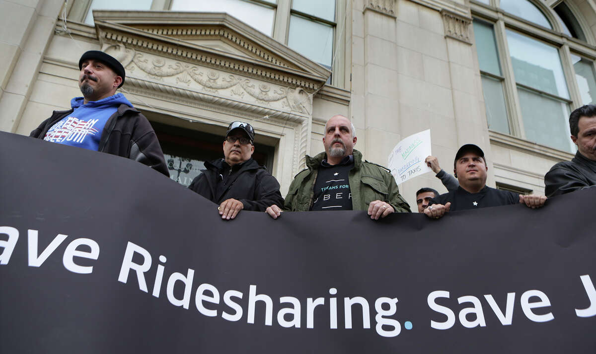 Ride sharing drivers hold a sign in front of City Hall Chambers where the city council will vote on changes to the city's vehicle-for-hire ordinance. Thursday, March 5, 2015.