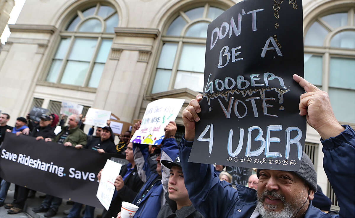 Jaime Pagan, right, an Uber driver, holds a sign with other ride sharing drivers in front of City Council Chambers where the city council votes on changes to the city's vehicle-for-hire ordinance. Thursday, March 5, 2015.