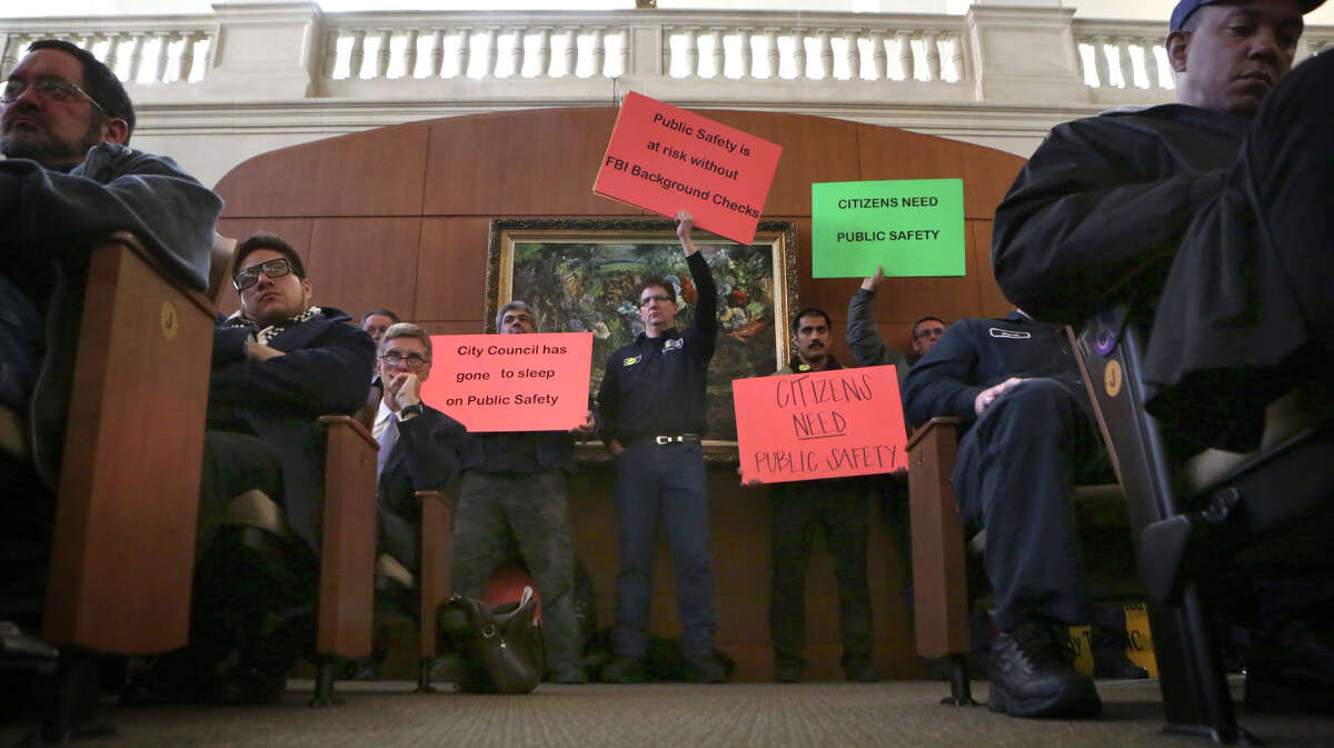 Taxi company employees hold signs at City Hall before the city council votes on changes to the city's vehicle-for-hire ordinance. Thursday, March 5, 2015.