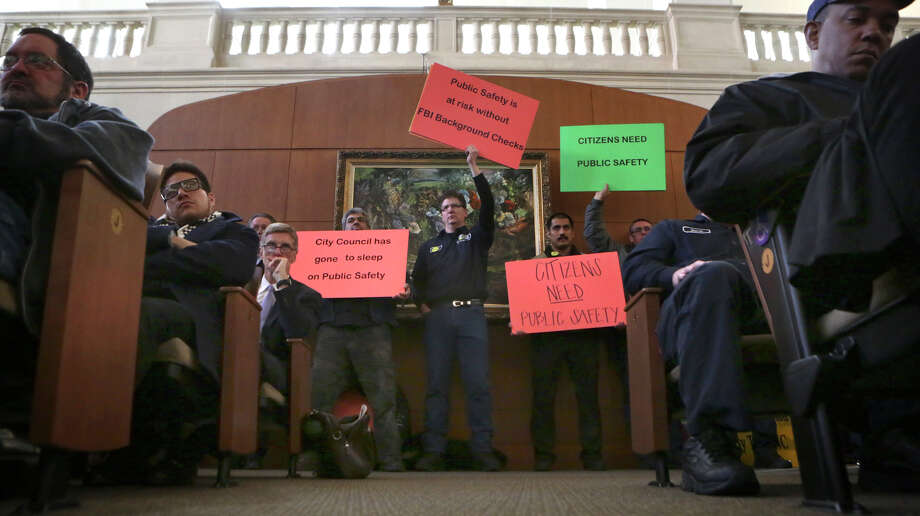 Taxi company employees hold signs at City Hall before the city council votes on changes to the city's vehicle-for-hire ordinance.  Thursday, March 5, 2015. Photo: Bob Owen, San Antonio Express-News / ©2015 San Antonio Express-News