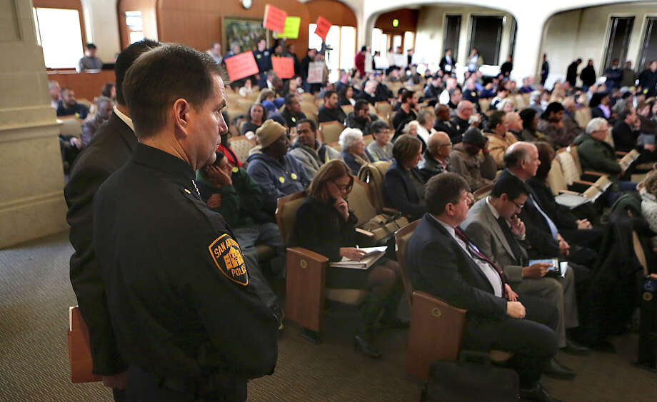 San Antonio Chief of Police Anthony Trevino, left, looks over the full house in City Council Chambers where taxi drivers and transportation network drivers speak at City Hall before the city council votes on changes to the city's vehicle-for-hire ordinance.  Thursday, March 5, 2015. Photo: Bob Owen, San Antonio Express-News / ©2015 San Antonio Express-News
