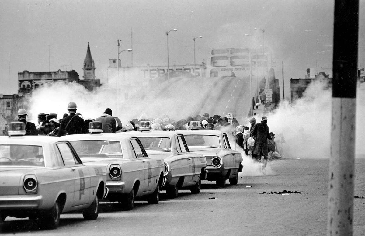 """Clouds of tear gas fill the air as state troopers, ordered by Gov. George Wallace, break up a demonstration march in Selma, Ala., on what became known as """"Bloody Sunday."""" The incident is widely credited for galvanizing the nation's leaders and ultimately yielded passage of the Voting Rights Act of 1965."""