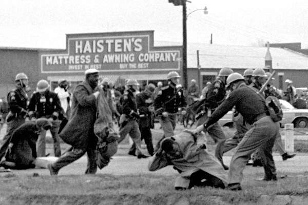 """FILE - In this March 7, 1965 file photo, state troopers use clubs against participants of a civil rights voting march in Selma, Ala. At foreground right, John Lewis, chairman of the Student Nonviolent Coordinating Committee, is beaten by a state trooper. The day, which became known as """"Bloody Sunday,"""" is widely credited for galvanizing the nation's leaders and ultimately yielded passage of the Voting Rights Act of 1965."""