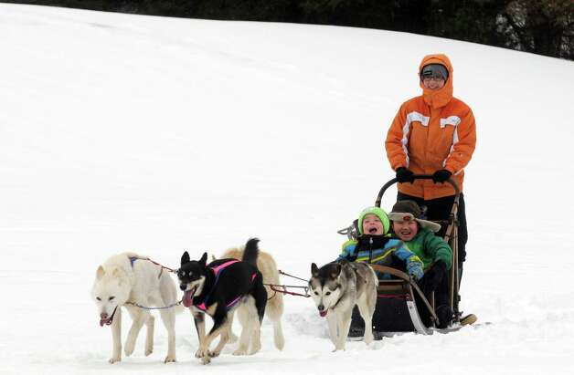 Saint Gregory's School first grade students T.J. Anderson, left, and Haruto Homma, right, get a ride on a dog sled driven by musher Kate Walrath on Thursday March 5, 2015, at Saint Gregory's School in Loudonville, N.Y. Saint Gregory?s classes will follow the progress of this year?s Iditarod race. The Kindergarten has prepared a map to help students track the race. The activities are design to help pupils learn about Alaska, and to experience how difficult the event is. Walrath owns a pet service called Run By Dogs, which offers sled dog excursions and educational programs. (Michael P. Farrell/Times Union) Photo: Michael P. Farrell / 10030850A