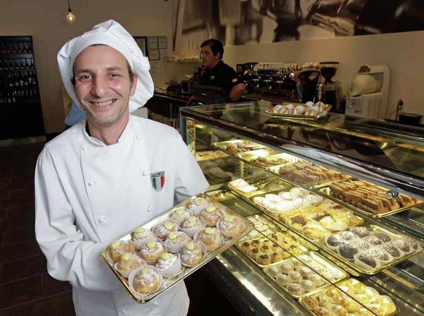 Pastry chef Giuseppe Montoro poses with a tray of Italian creme puffs at Fellini Caffe, 5211 Kelvin Dr., Tuesday, Oct. 29, 2013, in Houston. ( Melissa Phillip / Houston Chronicle )