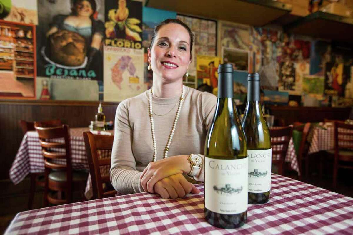 Brina D'Amico poses for a portrait with a pair of bottles of Paolo e Noemia d'Amico Calanchi Chaerdonnay on Friday, Feb. 13, 2015, in Houston. ( Brett Coomer / Houston Chronicle )