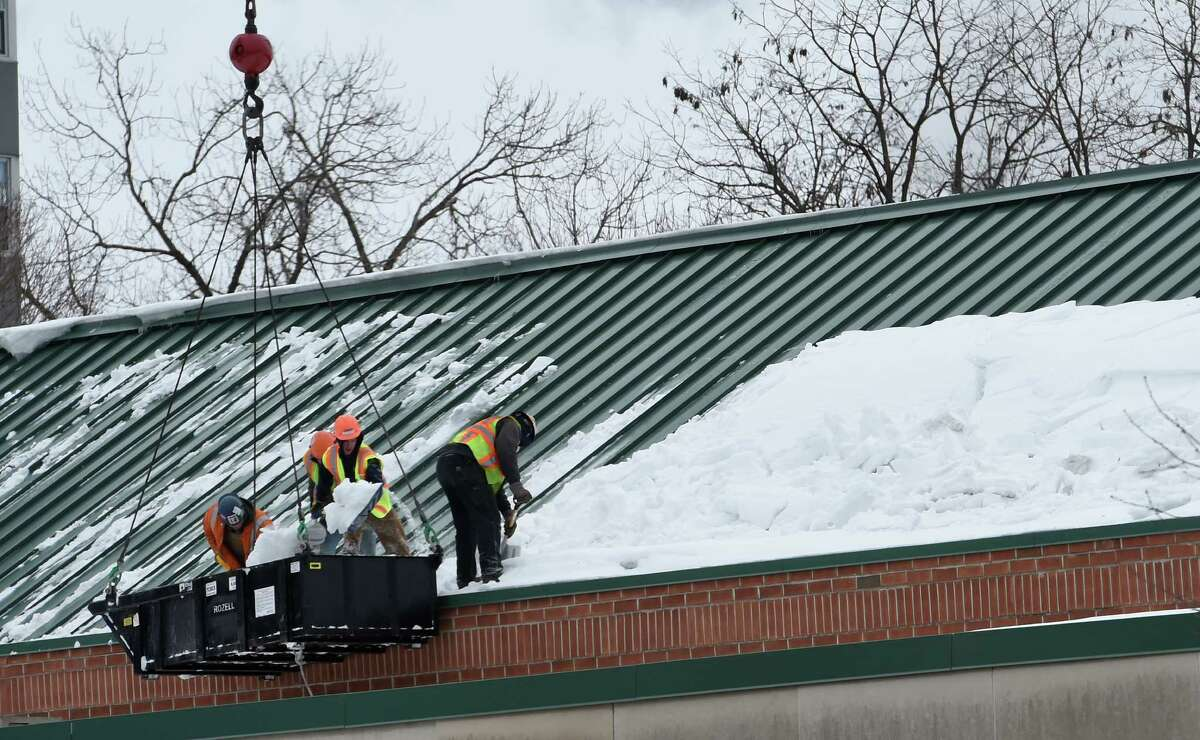 Workers clear the snow from the roof of the Glens Falls Civic Center Thursday afternoon March 5, 2015 in Glens Falls, N.Y. (Skip Dickstein/Times Union)