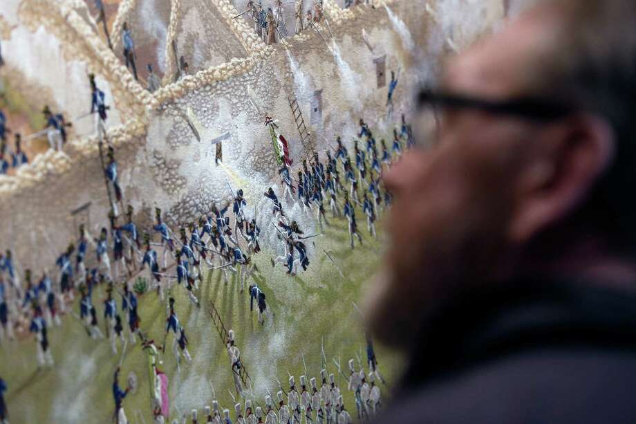 A person looks at a detail is seen Thursday Match 5, 2015 of artist Mark Lemon, one of the leading modern artists whose works focus on the Alamo mission and battle site, titled ÒThe Storming of the Alamo, March 6, 1836,Ó said to be the largest, most historically accurate detailed painting of the battle, at 8 feet tall and 15 feet wide. Lemon said it took him about 3,500 hours over 14 months to do the work. Photo: William Luther, San Antonio Express-News / © 2015 San Antonio Express-News