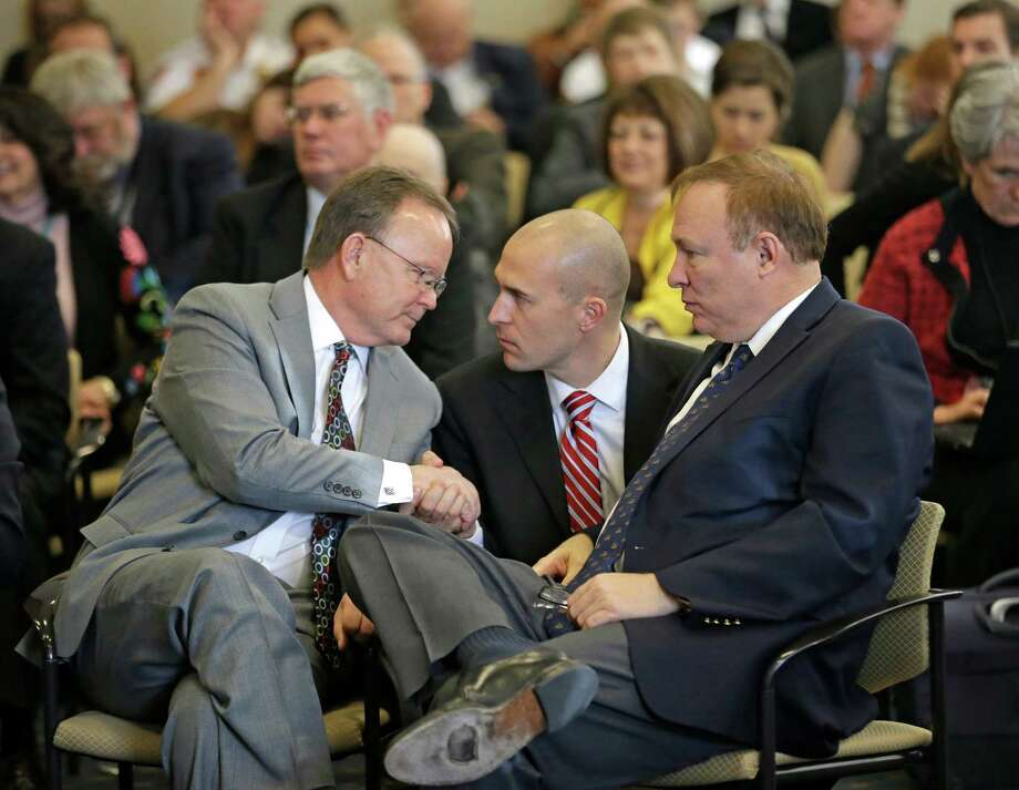 Eric Moutsos, center, the former Salt Lake Police officer who was placed on leave and later resigned for not wanting to ride his motorcycle in the Salt Lake gays pride parade for religious reasons, shakes hands with Sen. Stuart Adams, R-Layton, left, while Sen. Jim Dabakis, D-Salt Lake City, looks on during a committee hearing Thursday, March 5, 2015, in Salt Lake City. A landmark Utah proposal protecting gay and transgender individuals passed its test at the state Legislature Thursday when lawmakers on a Republican-controlled Senate committee offered their unanimous and at times emotional support of the measure.  (AP Photo/Rick Bowmer) Photo: Rick Bowmer, STF / AP