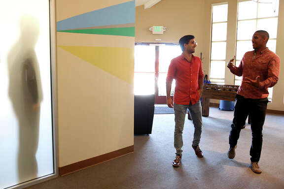 Symphony startup engineer Dhruv Dang (center) walks past part of the office wall mural with marketing analyst Jordan Smallwood in Palo Alto.
