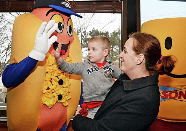 Sonic's Hot Dog mascot high fives 3-year old Joshua Bartholomew on his mother Tina during ceremonies for the new Sonic Drive-In site on Troy Schenectady Road Thursday March 5, 2015 in Colonie, NY. Originally from Texas, and a huge Sonic fan, Tina Bartholomew had launched a social media campaign to bring a Sonic to the Capital Region.  (John Carl D'Annibale / Times Union) Photo: John Carl D'Annibale / 10030863A
