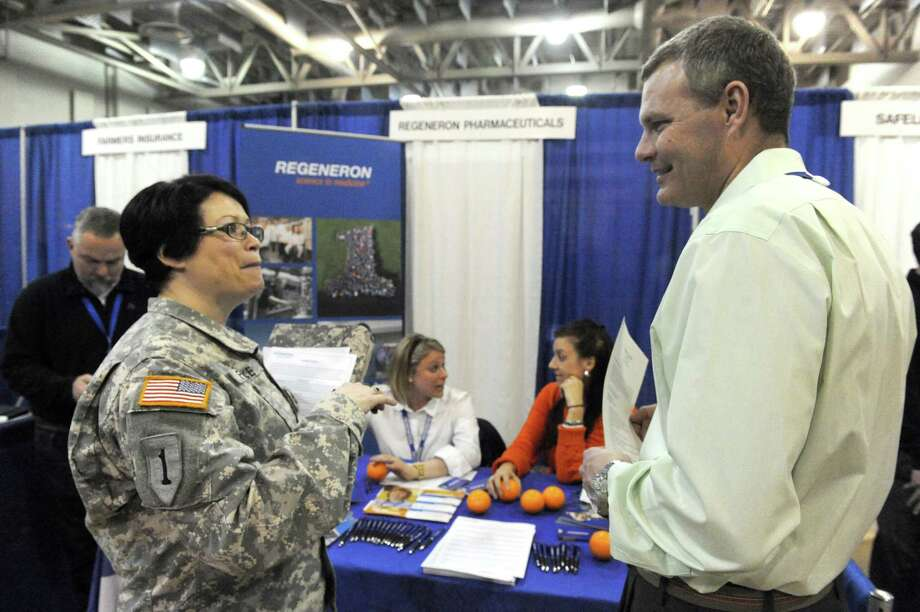 Army Sgt. Stephanie Fiebke, left, talks with George Berg with Regeneron pharmaceuticals as the New York National Guard hosted a Hiring Our Heroes Veterans' Job Fair at the Division of Military and Naval Affairs Headquarters on Thursday March 5, 2015 in Latam, N.Y.  (Michael P. Farrell/Times Union) Photo: Michael P. Farrell / 00030895A