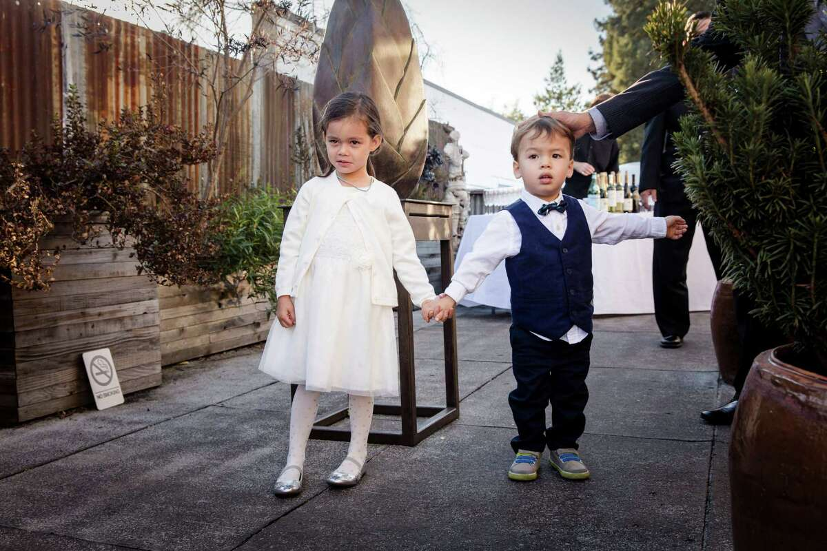 Madeleine Gibson, age 4, and Lukas Weber, age 2 1/2, preparing for their roles as flower girl and ring bearer at the wedding of Phuong Quach and Brian Thoms in Oakland.