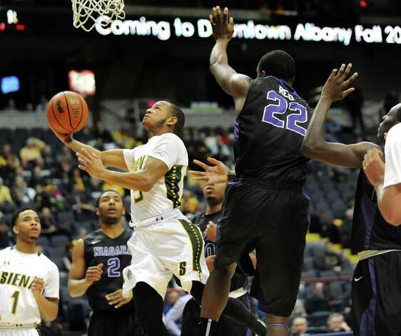 Siena's Evan Hymes, center, goes to the hoop as Niagara's Dominique Reid defends during their first round game in the MAAC Championship on Thursday, March 5, 2015, at Times Union Center in Albany, N.Y. (Cindy Schultz / Times Union) Photo: Cindy Schultz / 10030857A