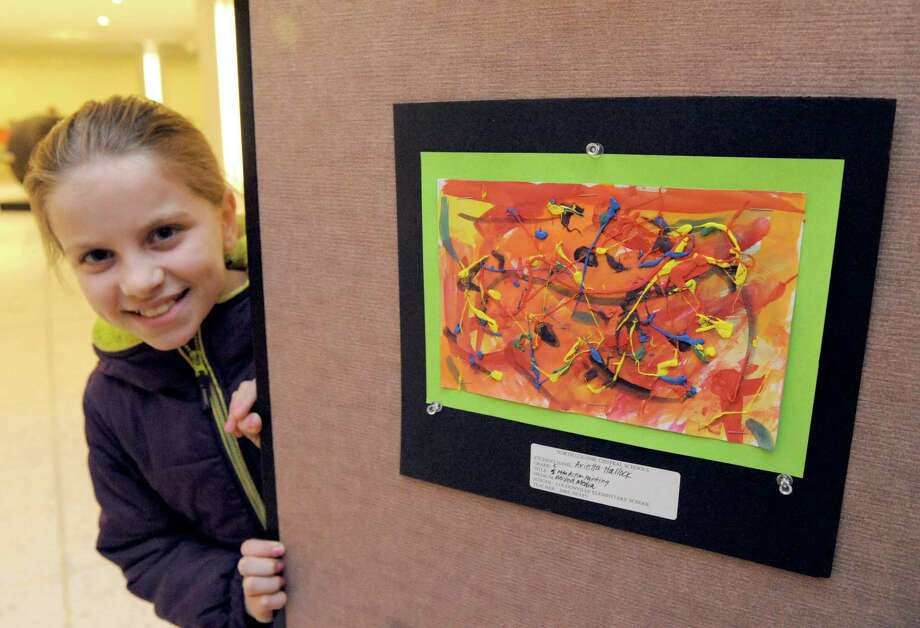 10-year-old Arietta Hallock a fifth grade student at Loudonville Elementary poses with her mixed media action painting influenced by abstract impressionist Jackson Pollack on display in the sixth annual Plaza Art student art exhibit in the south concourse of the Empire State Plaza on Thursday March 5, 2015 in Albany, N.Y.  (Michael P. Farrell/Times Union) Photo: Michael P. Farrell / 10030879A