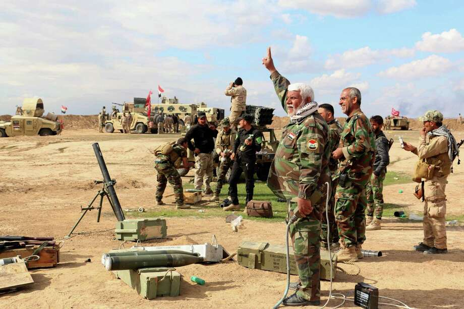 Iraqi soldiers and volunteers prepare to launch strikes Thursday against Islamic State militants outside Tikrit, 80 miles north of Baghdad. The militants reportedly have bulldozed the site of the ancient city of Nimrud. Photo: Uncredited, STR / AP