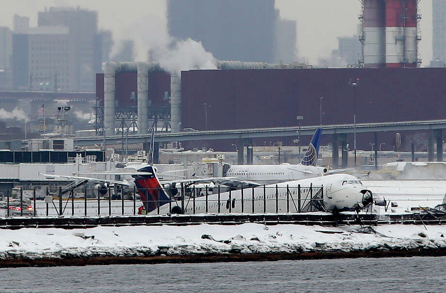 A plane that skidded off the runway at LaGuardia Airport hangs over the edge of the runway in New York, Thursday, March 5, 2015. The plane, from Atlanta, skidded off the runway while landing, and crashed through a chain-link fence. (AP Photo/Seth Wenig) ORG XMIT: NYSW106 Photo: Seth Wenig / AP