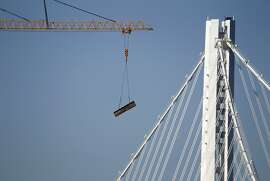 A crane removes a section of steel girder sliced from the old Bay Bridge span as demolition work continues in Oakland, Calif. on Thursday, March 5, 2015. The Toll Bridge Program Oversight Committee is scheduled to meet today to discuss cost overruns and potential delays in the demolition project.