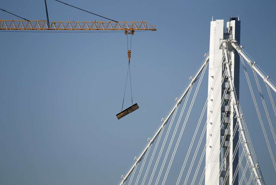 A crane removes a section of steel girder sliced from the old Bay Bridge span as demolition work continues in Oakland, Calif. on Thursday, March 5, 2015. The Toll Bridge Program Oversight Committee is scheduled to meet today to discuss cost overruns and potential delays in the demolition project. Photo: Paul Chinn, The Chronicle