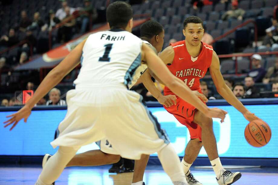 Fairfield's Marcus Gilbert, right, controls the ball as Saint Peters' Mohamed Farih, left, and Simeon Dennis defend during their first round game in the MAAC Championship on Thursday, March 5, 2015, at Times Union Center in Albany, N.Y. (Cindy Schultz / Times Union) Photo: Cindy Schultz / 10030857A