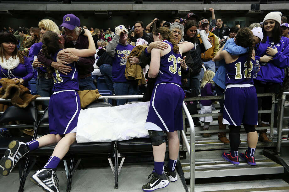 D'Hanis players from left, Jacie Henefey, Shelby Gayre and Sarah Craft get hugs from supporters after their loss against Nazareth in the 1A State Semifinals at the Alamodome, Thursday, March 5, 2015. Nazareth won, 61-18 to advance to the state finals on Saturday. Photo: JERRY LARA, Staff / San Antonio Express-News / © 2015 San Antonio Express-News