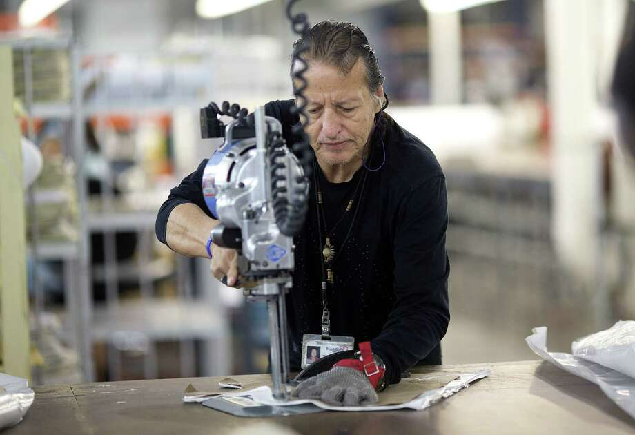 Adolfo Garzon cuts pieces for body armor at the Point Blank Body Armor factory in Pompano Beach, Fla. U.S. productivity for 2014 was up 0.7 percent. Photo: J Pat Carter, STF / AP