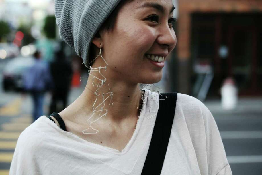Toshi Yamada wears earrings her boyfriend made at Polk and Bush streets. Photo: Sophia Germer / The Chronicle / ONLINE_YES
