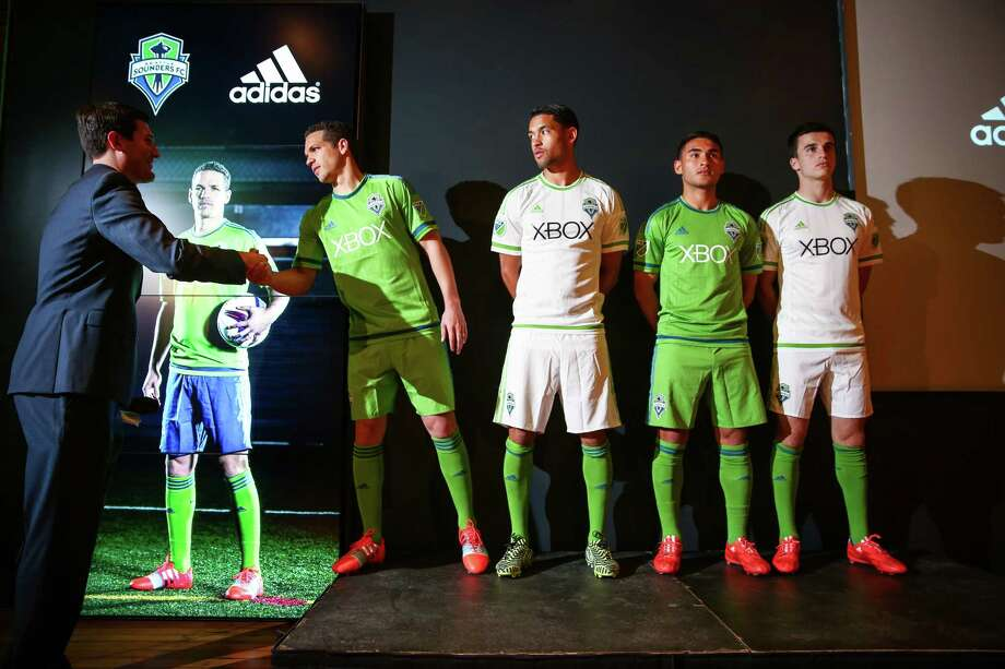 "Seattle Sounders players, from left, Osvaldo Alonso , Lamar Neagle, Cristian Roldan, and Aaron Kovar show the new Seattle Sounders uniforms as they are greeted by play-by-play announcer Ross Fletcher during an unveiling at ""THE NINETY,"" the Sounders' front office and event space in Pioneer Square on Thursday, March 5, 2015. Photo: JOSHUA TRUJILLO, SEATTLEPI.COM / SEATTLEPI.COM"