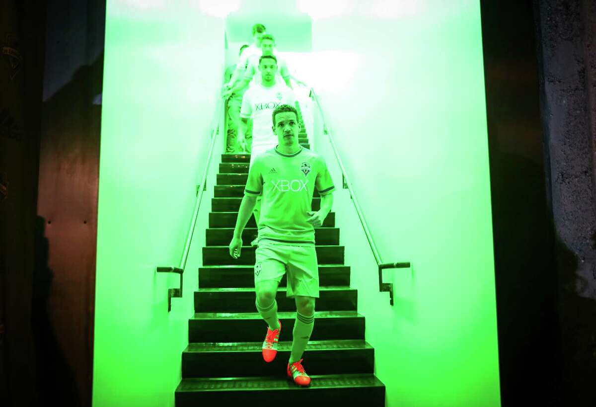 Seattle Sounders players are led by Osvaldo Alonso down stairs illuminated by green lights during an unveiling at
