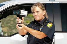 Female Police Officer checking vehicle speed with radar gun