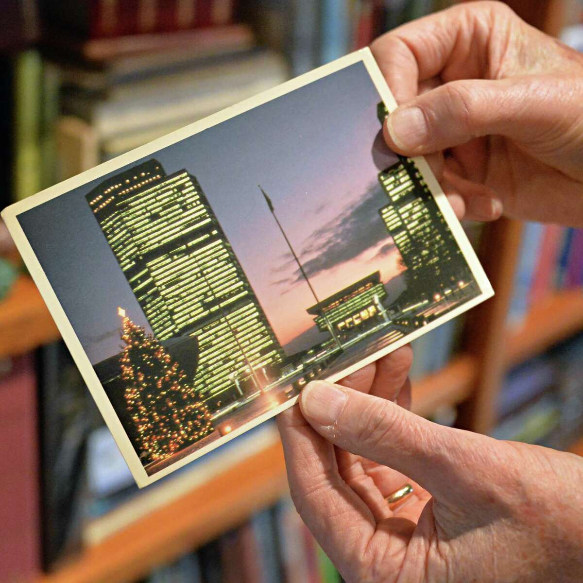 Robert Drew, a deltiologist or postcard collector, holds a postcard of the Empire State Plaza Friday Dec. 5, 2014, in Albany, NY. (John Carl D'Annibale / Times Union) ORG XMIT: ALB1412051630346968