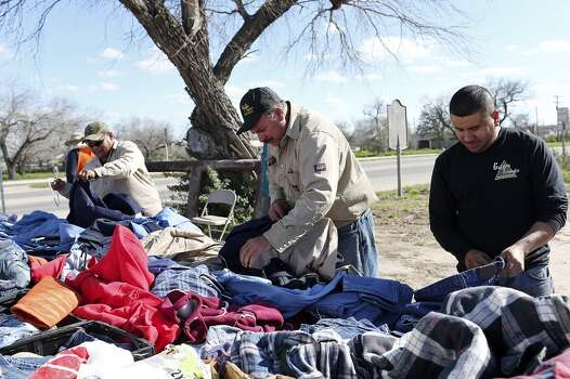 From left, Juan Fuentes, Daniel Sanchez and Abe Jimenez, from Laredo, look over used  resistant clothing at a stall in a parking lot in Tilden, Texas, Thursday, February, 19, 2015. According to the stall owner, sales for such product had dropped by 40-percent. Martinez also mentioned that less traffic is seen in the area that was highly congested with oil related vehicles. A drop in the price of crude oil from has led to lower prices at the pump for consumers. Hovering close to $50 from a high of over $100 per barrel of oil has led to a slow down activity in the Eagle Ford Shale play. Photo: JERRY LARA, San Antonio Express-News