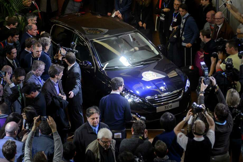 """A Peugeot 308  model car is displayed on March 3, 2014 after it was awarded """"Car of the year 2014"""" on the eve of the press day of the Geneva Motor Show in Geneva. Photo: FABRICE COFFRINI, AFP/Getty Images / 2014 AFP"""
