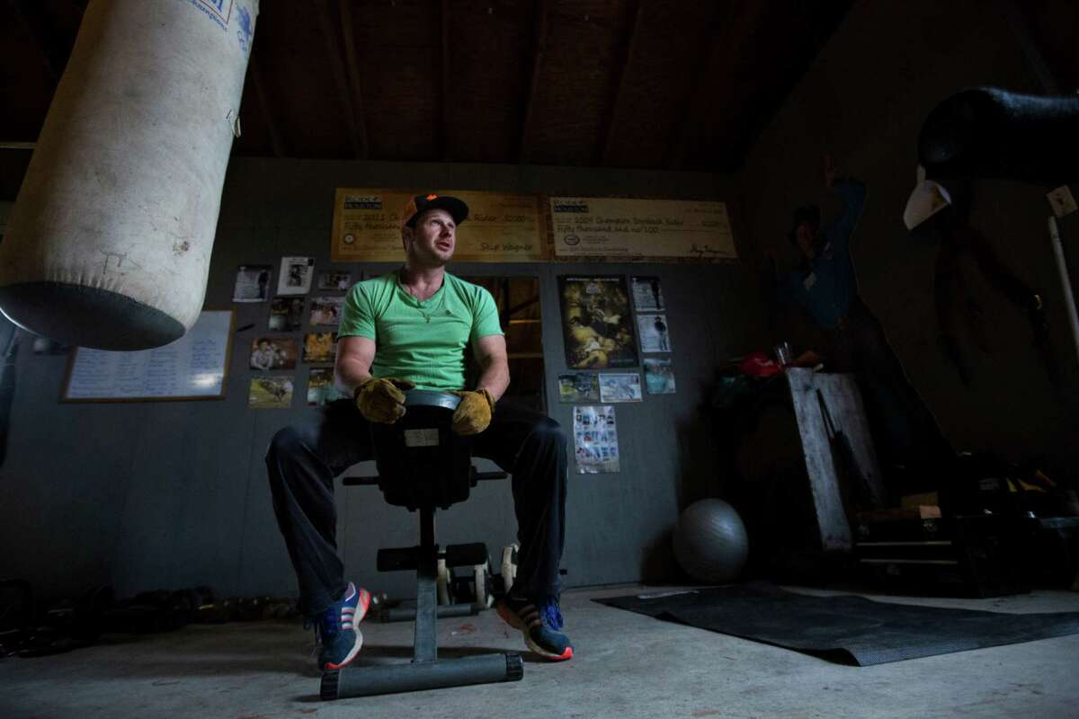 Champion bareback cowboy Clint Cannon takes a break from working out in his gym near his home in Waller. Cannon filled the space with the exercising tools to strengthen his body to perform better and also to protect it against injuries. Thursday, March 5, 2015.