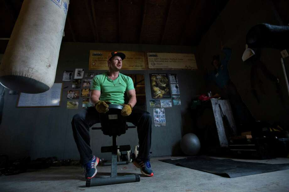 Champion bareback cowboy Clint Cannon takes a break from working out in his gym near his home in Waller. Cannon filled the space with the exercising tools to strengthen his body to perform better and also to protect it against injuries. Thursday, March 5, 2015. Photo: Marie D. De Jesus, Houston Chronicle / © 2015 Houston Chronicle
