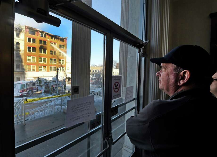Schenectady Mayor Gary McCarthy watches from the front door of City Hall as firefighters wet down hot spots after a fire consumed three buildings on Jay Street Friday morning, March 6, 2015, in Schenectady, N.Y.    (Skip Dickstein/Times Union) Photo: SKIP DICKSTEIN