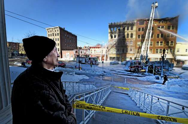 Benjamin Morales watches a firefighters wet down hot spots including his jewelry business after a multi alarm fire on Jay Street Friday morning, March 6, 2015, in Schenectady, N.Y.   (Skip Dickstein/Times Union) Photo: SKIP DICKSTEIN