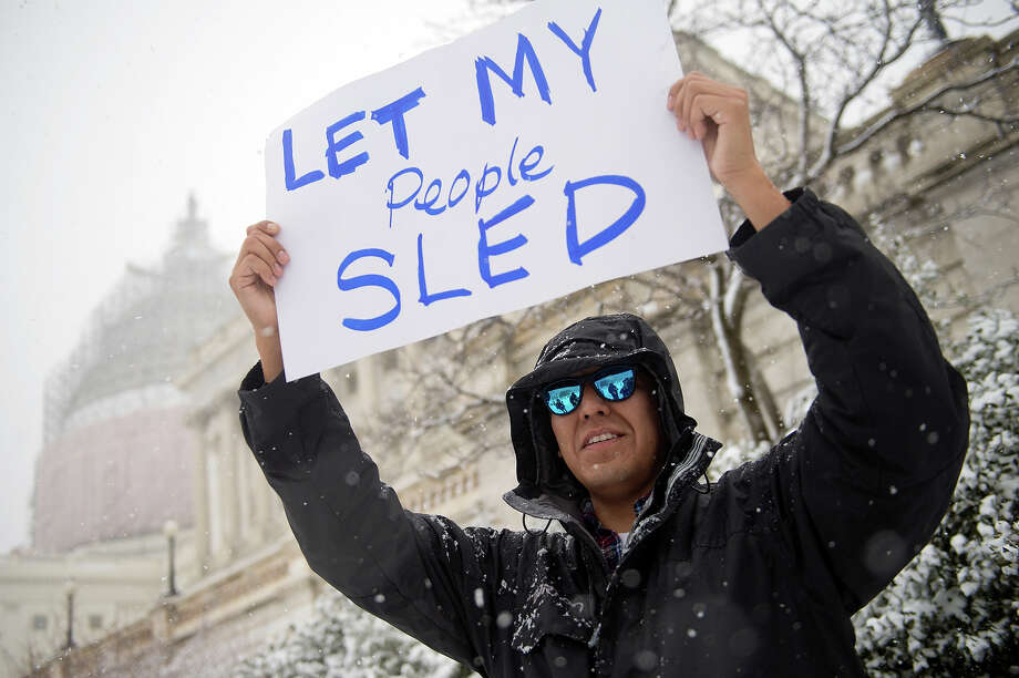 Hill staffer Brandon Ashley holds a sign of protest on the west front lawn of the Capitol during a snow storm, March 5, 2015. The Capitol Police informed people gathering of the ban on sledding in the area but most choose to ignore the warning. Photo: Tom Williams, CQ-Roll Call,Inc. / 2015 CQ-Roll Call, Inc.