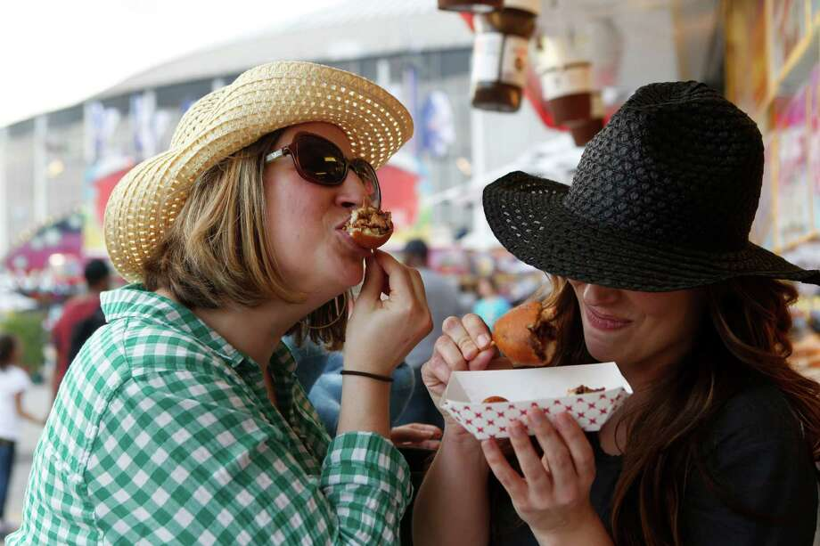 Jenni Miller, from Ohio, and Leigh Hamilton eat deep-fried bacon-wrapped Reese's Peanut Butter Cups. Photo: Jon Shapley, Staff / © 2015 Houston Chronicle