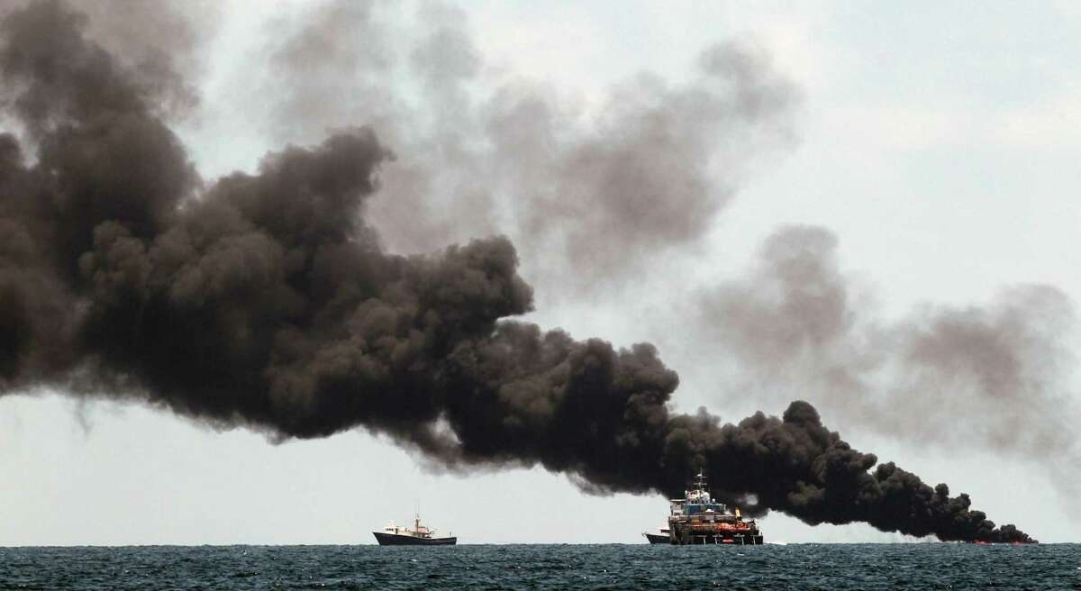 Vessels monitor a oil burn in the area of the Deepwater Horizon disaster on the Gulf of Mexico, Tuesday, July 13, 2010. BP officials have placed a containment cap over the leak in hopes that the flow of oil will be diminished. (AP Photo/Dave Martin)